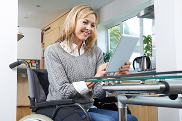 Woman in a wheelchair using a tablet computer